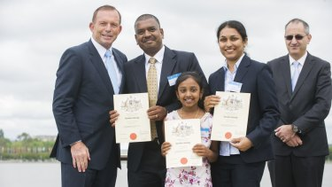Tony Abbott has his photograph taken in 2015 with a family who took out Australian citizenship after immigrating from India.