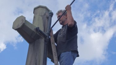 A photo of a Catholic Worker movement member removing the sword from the Cross of Sacrifice on Ash Wednesday in 2017.