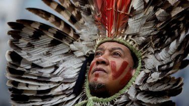 A leader of an indigenous community in Brazil protests forest destruction in Brussels last year. Activists say indigenous people across the Amazon are the environment's last line of defence.