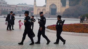 Security personnel on patrol outside a mosque attended by Uighurs in Xinjiang.