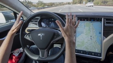 A member of the media test drives a Tesla Motors Model S car equipped with autopilot.