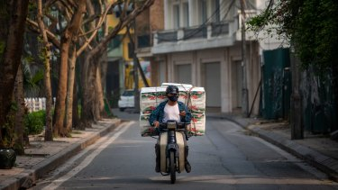 A delivery man with a load of toilet paper rides past the quarantined area of Truc Bach Street in Hanoi, Vietnam.