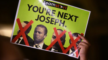 A protester holds up a poster of, from left, former chief of staff to the PM Keith Schembri, Prime Minister Joseph Muscat, Economy Minister Christian Cardona and former tourism minister Konrad Mizzi.