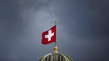 The Swiss flag above Switzerland's parliament building in Bern: The country could be labelled a currency manipulator.