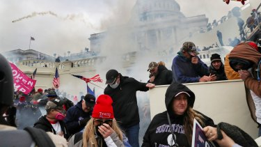 Supporters of U.S. President Donald Trump cover their faces to protect from tear gas during a clash with police officers in front of the U.S. Capitol Building in Washington.