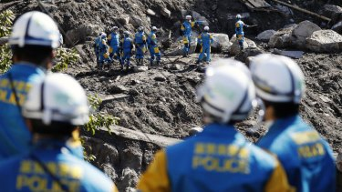 Rescuers search for missing persons at the site of a landslide in Marumori, near Fukushima.