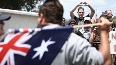 A supporter of the Rally Against Racism responds to a Reclaim Australia Rally supporter, in front of Parliament House in Canberra in 2015.