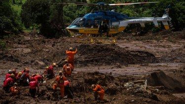 Rescue workers co-ordinate with a helicopter while attempting to remove a body from the debris of a bus after the dam burst in Brazil.