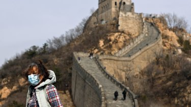A woman wearing a protective face mask visits the Badaling Great Wall of China after it reopened for business.