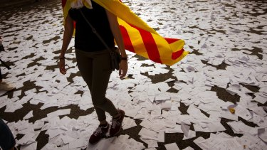 A Catalan independence supporter walks a long a street covered with referendum ballots during a rally in front of the then Spanish Partido Popular ruling party headquarters in Barcelona, Spain, in 2017.