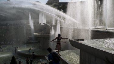 People cool down in the fountains of the Trocadero gardens in Paris on July 25 last year, when the temperature hit 42.6 degrees, a record for the French capital.