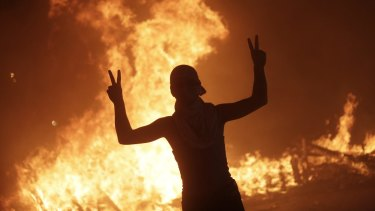 An anti-government protester makes victory signs in front a fire set by protesters to block a road during a demonstration in Beirut, Lebanon.