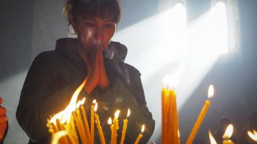 A woman lights candles inside a church of the Dadivank, an Armenian Apostolic Church monastery dating to the 9th century, as ethnic Armenians leave the separatist region of Nagorno-Karabakh to Armenia.