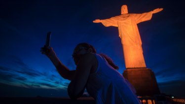 A tourist takes a selfie with the Christ the Redeemer. The tourist attraction has been closed due to coronavirus.