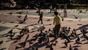 Children feed pigeons in Barcelona.