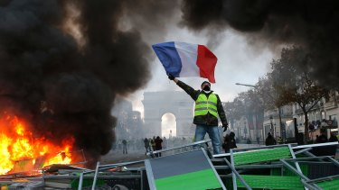 A demonstrator waves the French flag near a burning barricade on the Champs-Elysees on  Saturday.