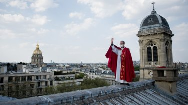 Father Bruno Lefevre Pontalis stands on the rooftop of Saint Francois Xavier church to bless the city of Paris during Easter.