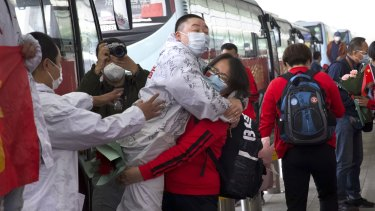 A medical worker, in red, embraces a colleague as she prepares leave Wuhan's main airport on Wednesday.