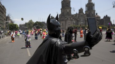 A street performer dressed as Batman takes a selfie during a protest in Mexico City.