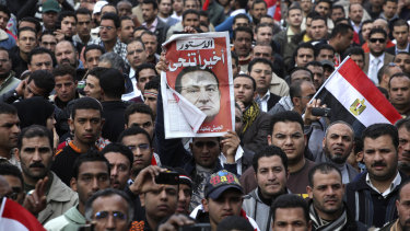 February, 12, 2011:  A protester holds up a sign that reads 'Finally he steps down' in Tahrir Square, Cairo.