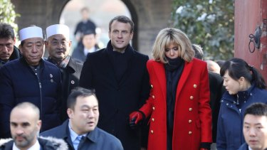 French President Emmanuel Macron, centre, and his wife Brigitte Macron, in red, visit the Great Mosque of Xian during a visit to the Great Mosque of Xian in northwestern China in 2018.