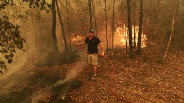 Michael Gate doing his best against the fury of the Green Wattle fire in Orangeville.