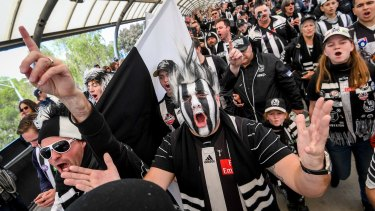Collingwood fans in full voice make their way to the MCG.