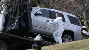 Crime scene investigators load a car that appears to have been checked for fingerprints onto a truck outside Francesco Cali's home.