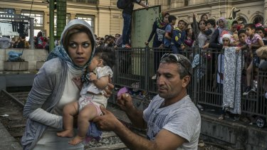 A migrant family gathers with a few hundred others waiting for a train to Germany at the Keleti train station in Budapest, September 2015.