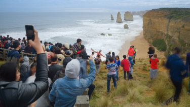Tourists pose for photos outside the designated viewing area for the Twelve Apostles at Port Campbell weeks ago.