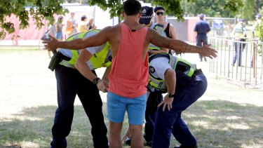 Police with sniffer dogs search people for drugs entering the Summadayze festival in Sydney.