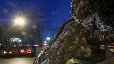 A statue of Albert Einstein sits in the shadow of the early morning commuter traffic in Washington.