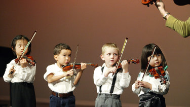Three-year-old violinists perform in a concert.