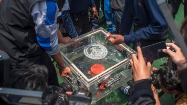 Members of the National Transportation Safety Committee lift a box containing the flight data recorder from the crashed Lion Air jet in November 2018.