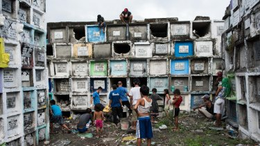 Shanty dwellers living inside the cemetery look at bodies being buried in Manila, Philippines.