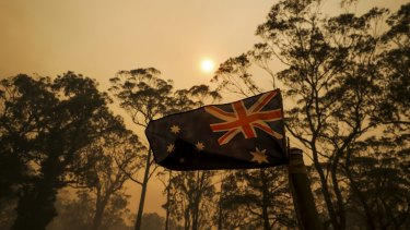 The Australian flag flies on a property as smoke from a bushfire approaches.