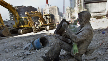 "A dust covered bronze statue of a man with his briefcase titled ""Double Check,"" by Seward Johnson, rests in the rubble of the World Trade Centre towers in New York after 9/11."
