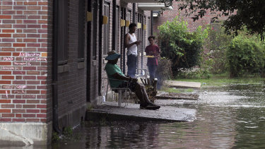 Residents at Trent Court Apartments wait out the weather as rising waters get closer to their doors.