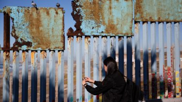 A woman takes pictures as birds sit along a rusted top section of the current US-Mexico border wall near the beach in Tijuana, Mexico.