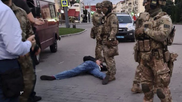 The assailant, who seized a long-distance bus with 10 hostages, lies on the ground after police officers captured him in the city centre of Lutsk.