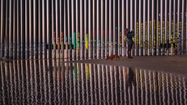 A woman takes a snapshot by the border fence between San Diego, Calif., and Tijuana, as seen from Mexico.