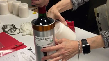 Researchers prepare bottles of French red wine to be flown aboard a Northrop Grumman capsule from Wallops Island, Virginia.