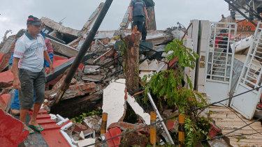 Residents inspect earthquake-damaged houses in Mamuju, West Sulawesi, on Friday.