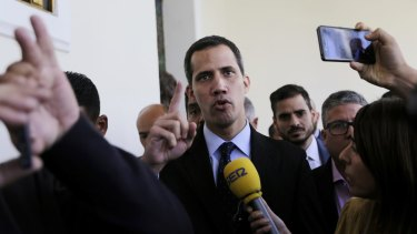 Opposition National Assembly President Juan Guaido, centre,  has declared himself interim president of Venezuela.