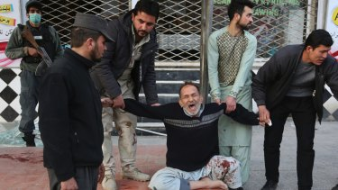 A relative of a victim is helped as he cries after a deadly suicide attack in Kabul on January 27, 2018.