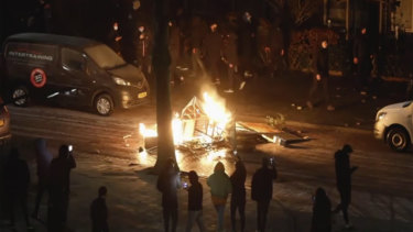 People use their phones to film items burning on a fire started by rioters, in Haarlem, Netherlands.