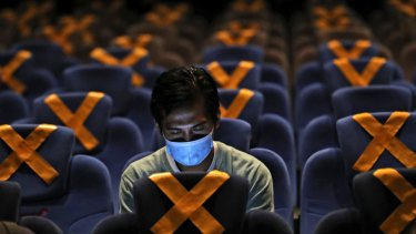 A man checks his mobile phone as he sits amid physical distancing markers prior to the start of a movie at the recently reopened CGV Cinemas theatre in Jakarta, Indonesia, last month.