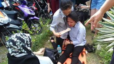 A woman on a stretcher is assisted after a powerful earthquake was felt in Davao City, Philippines, on Tuesday.