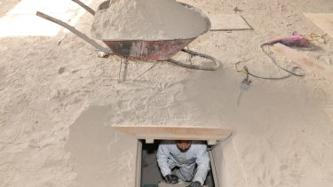 A forensics worker climbs up a ladder to the exit of the tunnel used by Guzman to escape from the Altiplano maximum security prison.