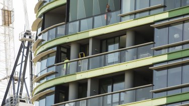 Tradesmen work on Opal Tower in Olympic Park which was evacuated in December.